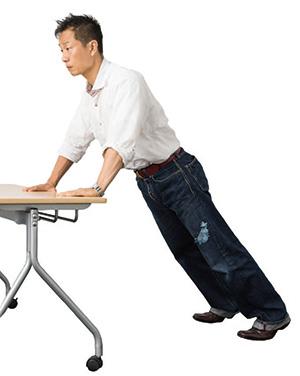 ①腕を肩幅より少し広く開き、デスクから1歩程度下がった位置で両手をつきます。